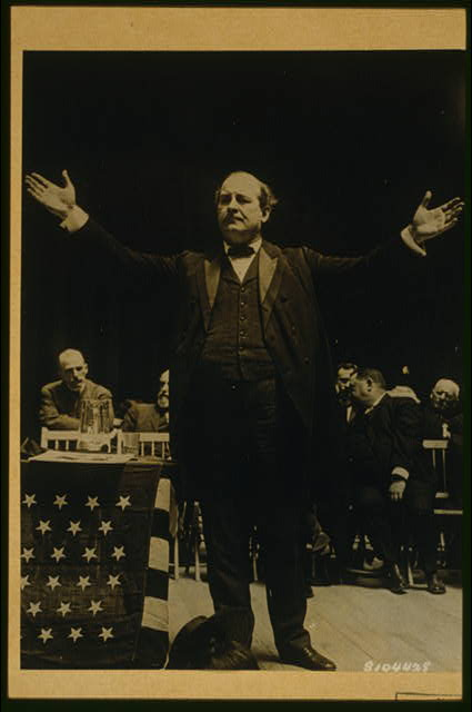 [William Jennings Bryan, full-length view with arms spread, standing next to flag drapped table on stage; men seated in the background, during 1908 Democratic National Convention]