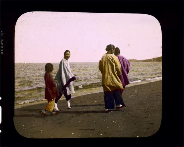 Four women walking along sea-shore