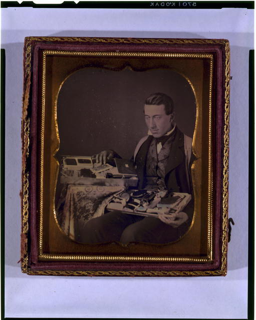 [Occupational portrait of a salesman, three-quarter length, seated, displaying his wares]
