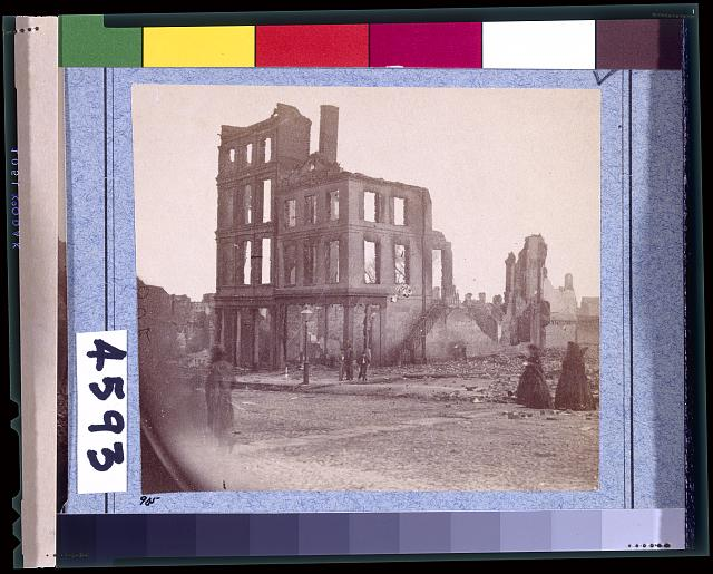 "[View in the ""Burnt District,"" Richmond, Va., showing two women dressed in black approaching shell of four-story building, gutted by fire]"