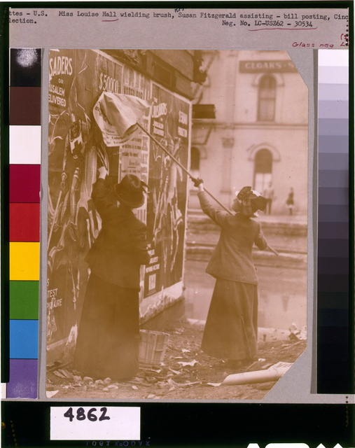 [Louise Hall, with brush, and Susan Fitzgerald pasting billboard posters, Cincinnati, May 1912]