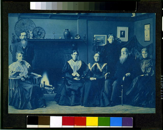 [Frances Benjamin Johnston posed with six members of her family, by fireplace, in her Washington, D.C. studio]