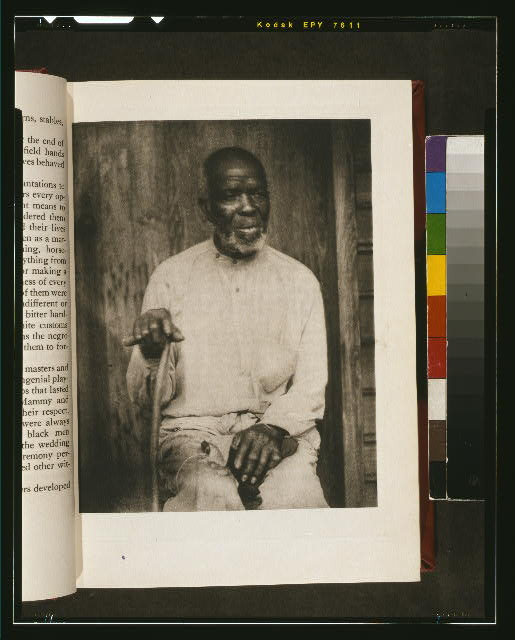 [African American man, three-quarter length portrait, seated, facing front, right hand holding cane, left hand on lap]