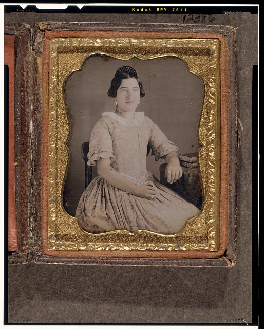 [Unidentified woman, three-quarters length portrait, seated, with arm resting on a table with tablecloth]