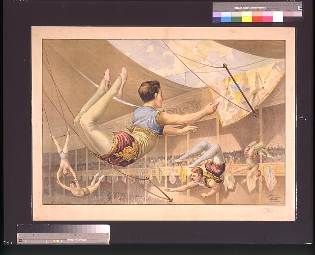 [Five male trapeze artists performing at a circus]