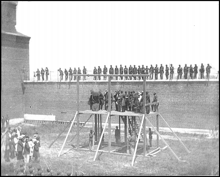 [Washington, D.C. The four condemned conspirators (Mrs. Surratt, Payne, Herold, Atzerodt), with officers and others on the scaffold; guards on the wall]