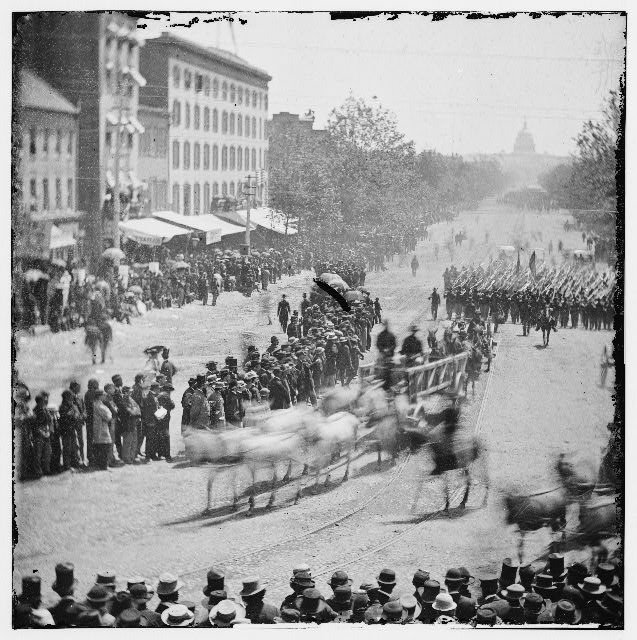 Washington, District of Columbia. Grand Review of the Army. Infantry unit with fixed bayonets followed by ambulances passing on Pennsylvania near the Treasury