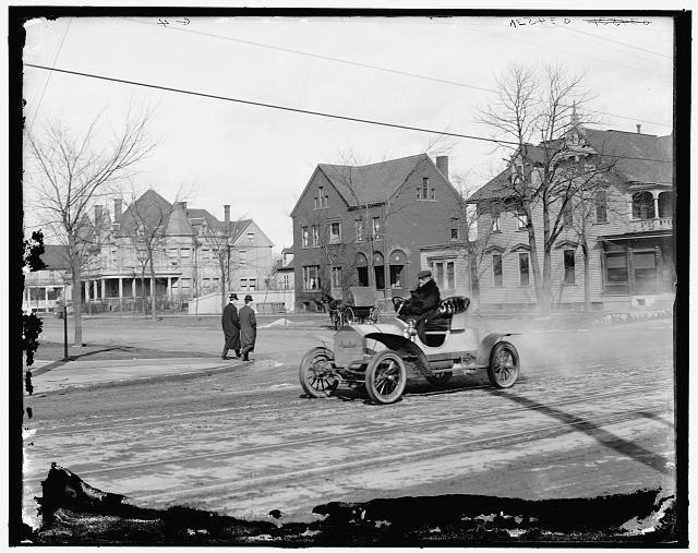 [Automobile on town street]