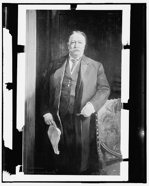 [William H. Taft, standing next to chair]