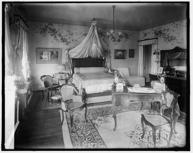 [Bedroom with draped bed and writing desk]