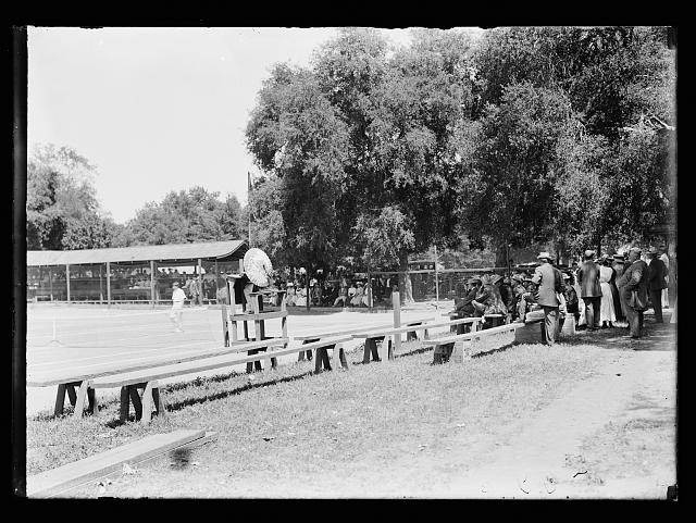 [Tennis match with onlookers, possibly at resort]