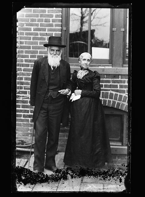 [Father and mother of William Henry Jackson, full-length portrait in front of house]