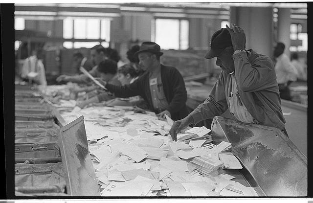 [African American postal employees sorting mail on table]