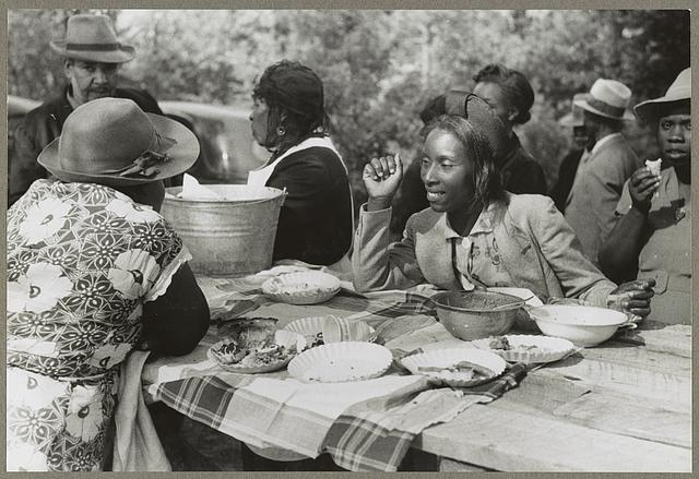 An outdoor picnic being held during the noon intermission of a meeting of ministers and deacons of the Negro church in Yanceyville, N.C. c1940