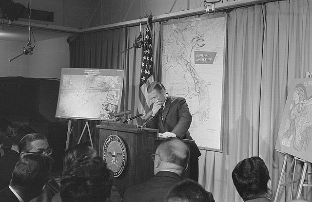 [Secretary of Defense, Robert McNamara standing at a podium in front of a map of Vietnam during a press conference]