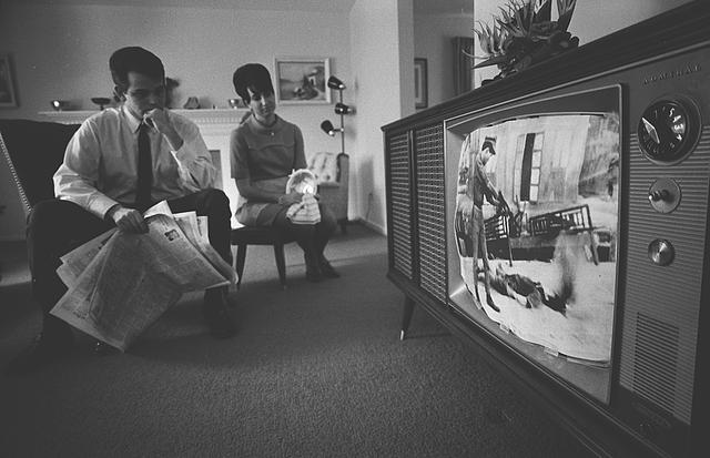 [A man and a woman watching a film footage of the Vietnam war on a television in their living room]