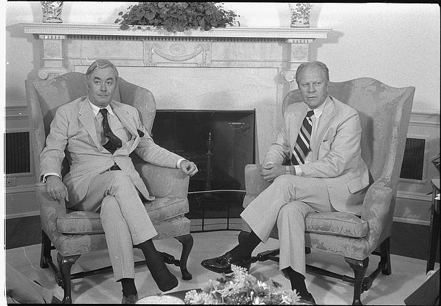 [UN Ambassador Daniel P. Moynihan and President Gerald Ford, seated in armchairs, in front of a fireplace]
