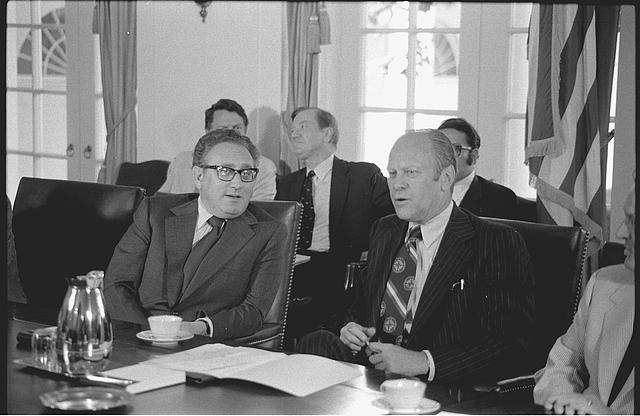 [Secretary of State Henry Kissinger and President Gerald Ford seated at a conference table in the White House, during a cabinet meeting]