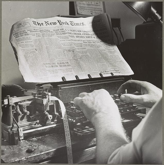 News room of the New York Times newspaper Copy readers at the telegraph desk which handles all dispatches from the U.S., outside New York city. Man wears hat because of draught.
