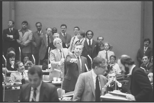 [Alderman Edward Vrdolyak (standing, center) gesturing during a meeting of the Chicago City Council with Mayor Harold Washington, as Alderman Edward M.  Burke stands behind him]
