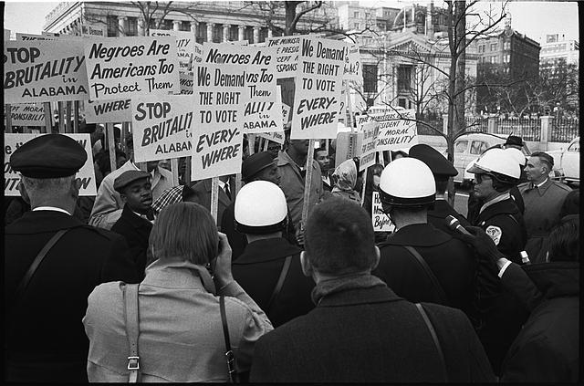 "[African American demonstrators outside the White House, with signs ""We demand the right to vote, everywhere"" and signs protesting police brutality against civil rights demonstrators in Selma, Alabama]"