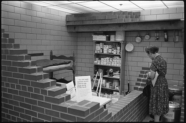 woman in bomb shelter with emergency supplies