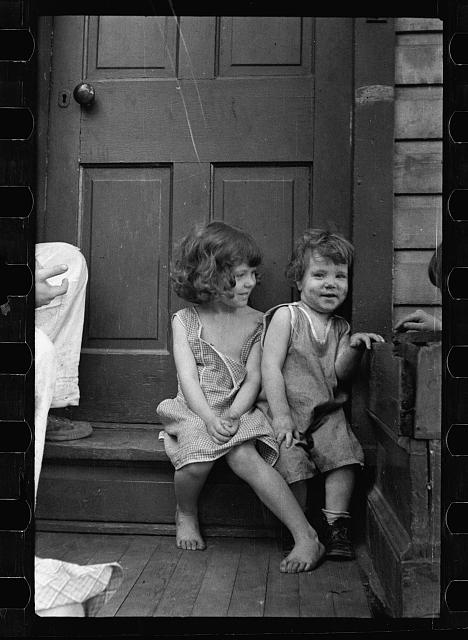 Small girls sitting in doorway of house in Georgetown, Washington, D.C.