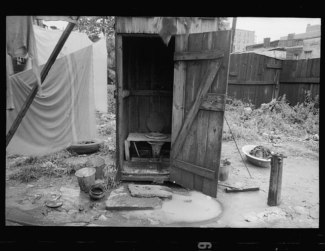 Backyard privy, Washington, D.C., near Government Printing Office. Puddle of water in front of privy. Pump on right supplies water for house in back of privy