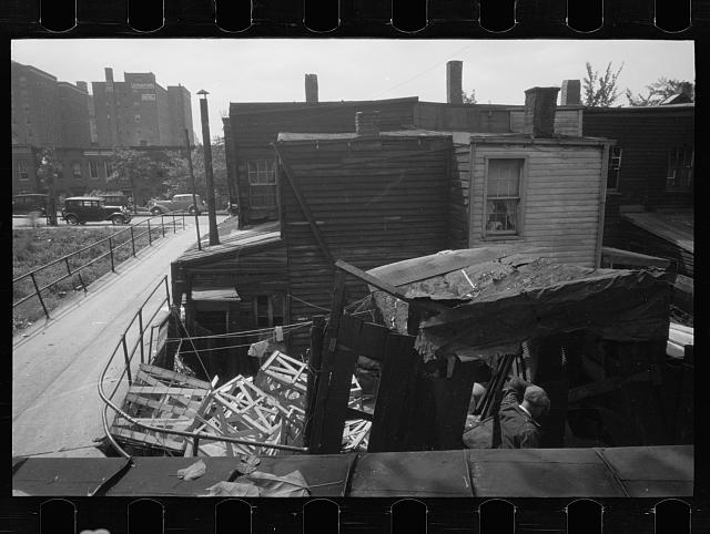 [Untitled photo, possibly related to: Negro backyard, Washington, D.C. Backyard near Stratford Hotel and within short distance from both the Capitol and Union Station, showing flooded yard and debris. In big rains, kitchen and bedroom floors of this house are so flooded that it is necessary to lay planks on them, the inhabitants say]