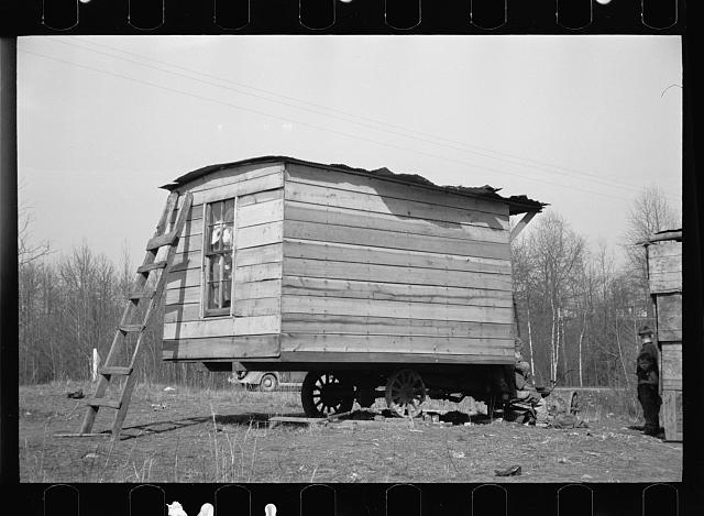 This one-room hut built of rough lumber over the chassis of an abandoned Ford truck was the housing provided by a landlord for an illiterate wood-cutter, with a wife and seven children. Found on U.S. Route 70 between Camden and Bruceton, Tennessee, near Tennessee River.  Family of nine lived and slept in this shack