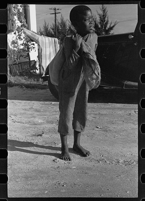 A Negro boy bringing away defective grapefruit from the Fort Pierce fruit canning plant, Florida