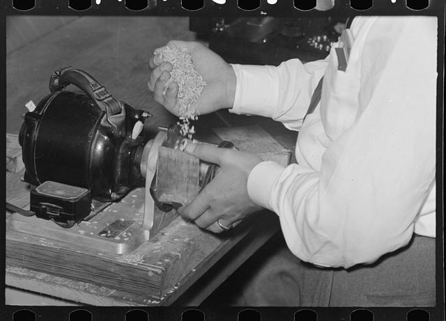 Placing sample of rice in milling machine for test, Crowley, Louisiana, state rice mill