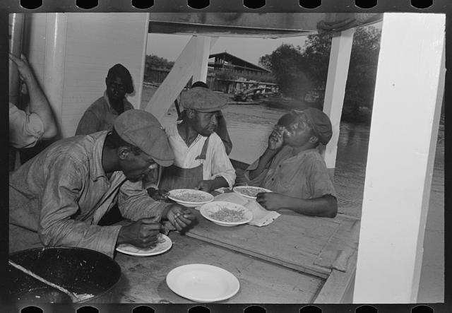 Negro stevedores eating on stern of boat. Food supplied to crew consists almost entirely of carbohydrates with some of the cheaper cuts of meat. Sleeping quarters are not provided for stevedores, who sleep in any available space