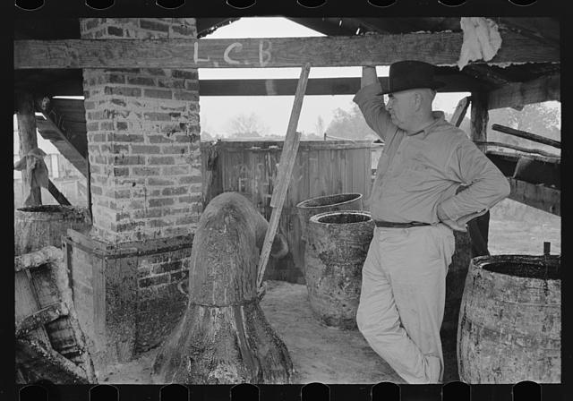 [Untitled photo, possibly related to: Owner atop his turpentine still. Goosneck runs from the still to the condenser coils where vapors are chilled. State Line, Mississippi]