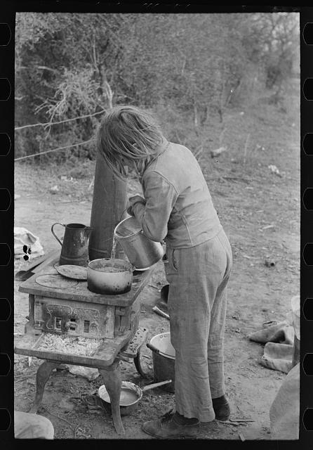 Child of white migrant adding water to boiling beans on stove which was set up immediately after reaching camping grounds near Harlingen, Texas