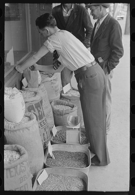 [Untitled photo, possibly related to: Clerk putting up seed, San Augustine, Texas]