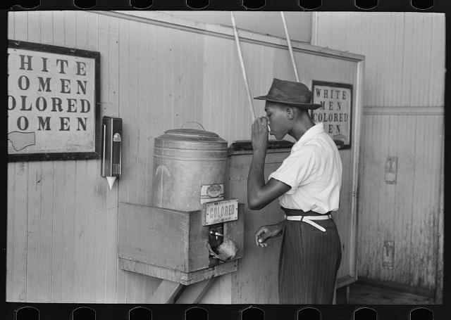 "Negro drinking at ""Colored"" water cooler in streetcar terminal, Oklahoma City, Oklahoma"