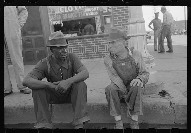 Negro and white man sitting on curb talking, Muskogee, Oklahoma