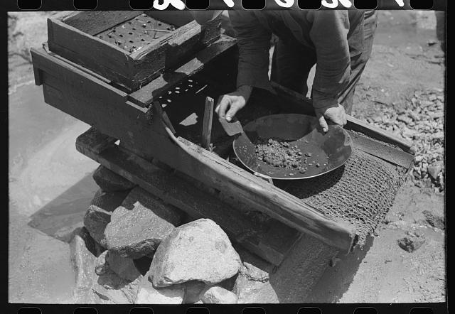 "[Untitled photo, possibly related to: Gold prospector pouring water through his ""rocker,"" Pinos Altos, New Mexico. He was born in Fremont, Nebraska on Eugene Fields's death day and so was named Eugene by a romantically minded mother. Pinos Altos, New Mexico]"
