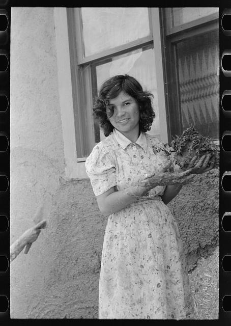 Spanish-American girl with handful of adobe plaster, Chamisal, New Mexico