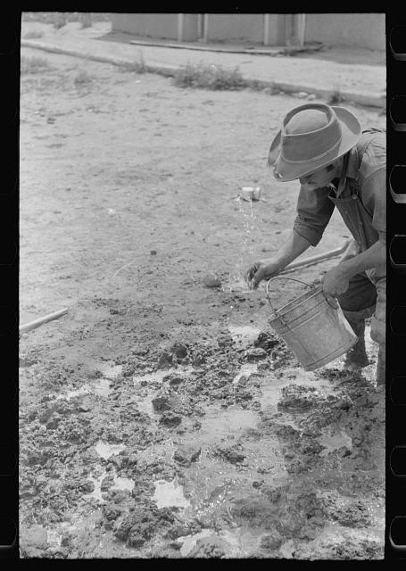 Spanish-American man adding water to plaster, Chamisal, New Mexico