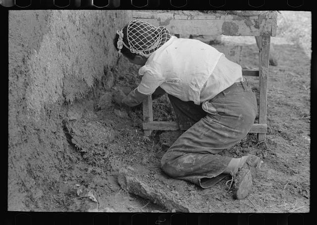 Plastering near the ground is carefully done, all old disintegrating plaster being removed. Chamisal, New Mexico