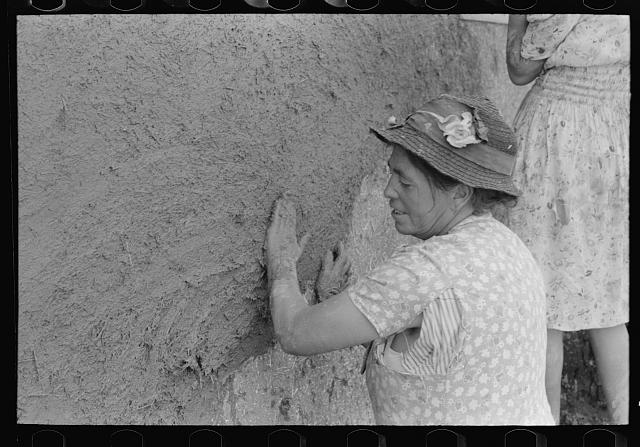 After plaster is applied with towel it is smoothed out with the hands. The women pride themselves on careful plastering, Chamisal, New Mexico
