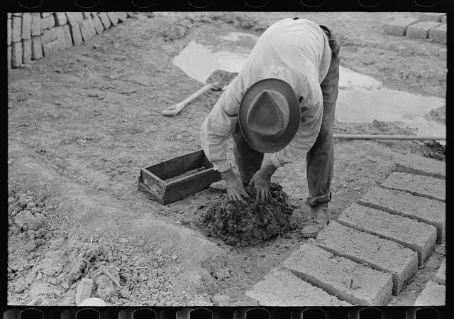 Mixing adobe for making bricks, Chamisal, New Mexico