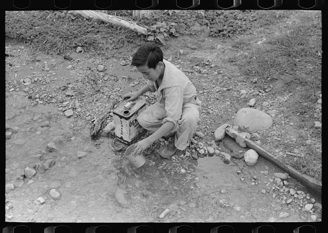 [Untitled photo, possibly related to: A Spanish-American boy dipping water from irrigating ditch. Water will be used in house for cooking, drinking, etc. Chamisal, New Mexico]
