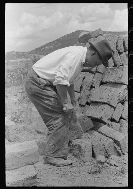 Removing the rough edges from adobe bricks with trowel, Penasco, New Mexico