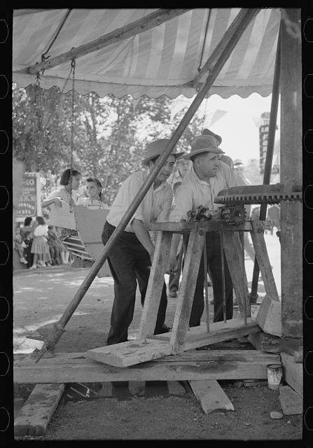 Power for the old-fashioned merry-go-round is furnished by two husky Spanish-American men, Taos, New Mexico