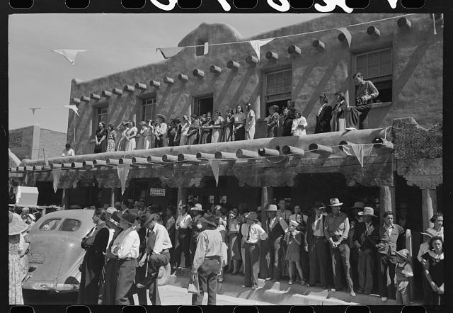 Crowds lined the streets and stood on top of covered sidewalks to see the dances at the fiesta, Taos, New Mexico