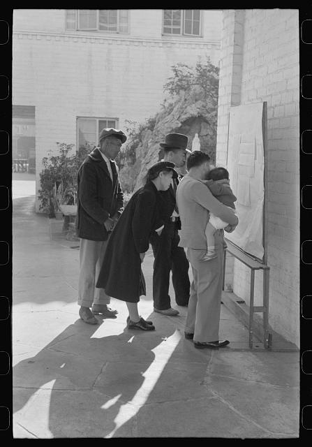 Los Angeles, California. Japanese-American evacuation from West Coast areas under U.S. Army war emergency order. Reading evacuation orders on bulletin board at Mary Knoll mission