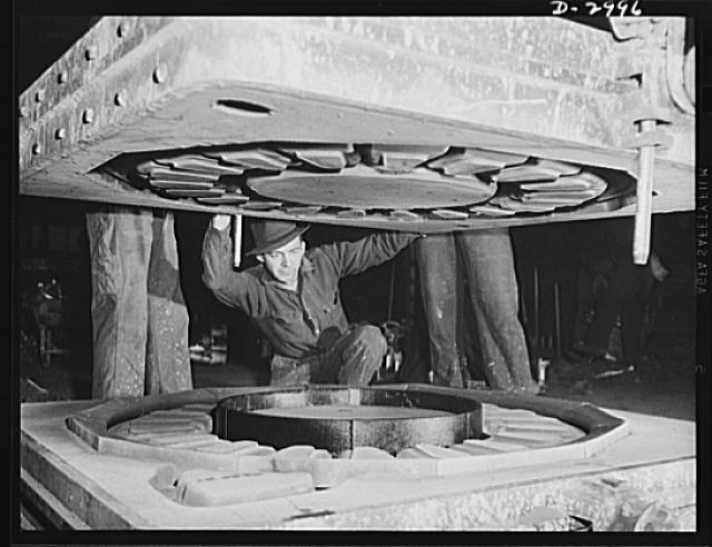Aluminum casting. It's a delicate operation, this closing of the cope on a large sand mold. When the parts are locked together, the molten aluminum is poured into the mold. Aluminum Industries Inc., Cincinnati, Ohio